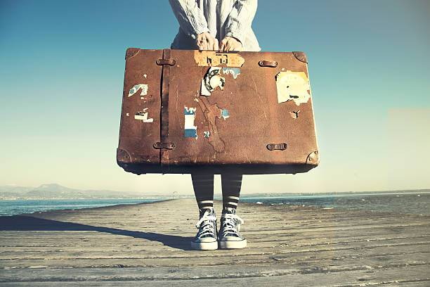 image: woman holding old suitcase
