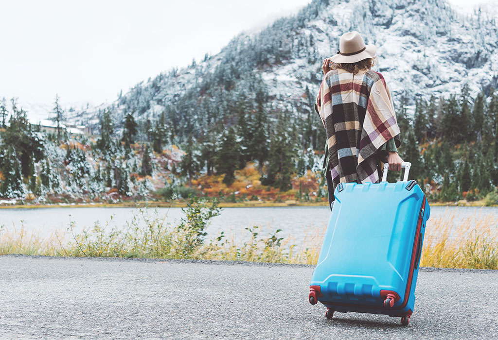 image: woman with suitcase winter mountains